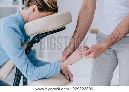 Masseur Doing Hands Massage For Businesswoman In Shirt