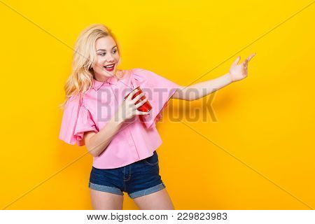 Portrait Of Attractive Laughing Blonde Woman With Red Lips In Pink Shirt And Jeans Shorts With Red P