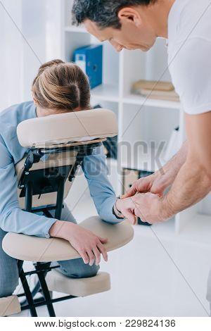 View Of Masseur Doing Hands Massage For Businesswoman