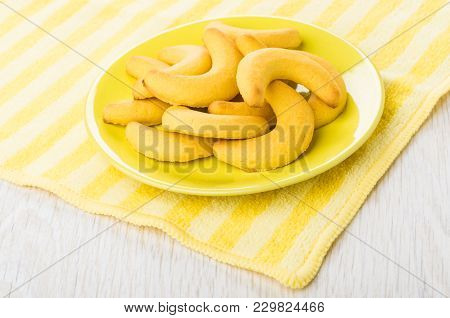 Shortbread In Form Crescent In Saucer On Yellow Napkin On Wooden Table