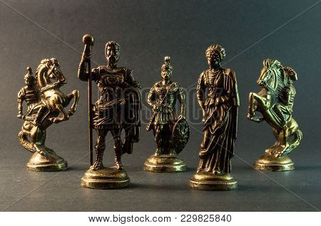 Metal Chess Pieces Of Roman Empire King And Queen And Army On Grey Background