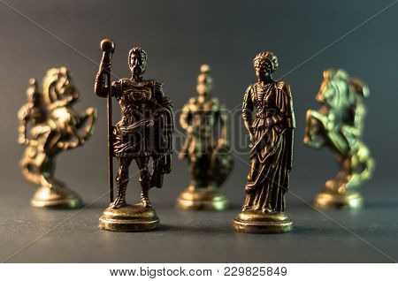 Metal Chess Pieces Of Roman Empire King, Queen And Army On Blurry Background