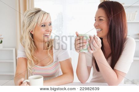 Laughing Women sitting at a table with cups in a kitchen