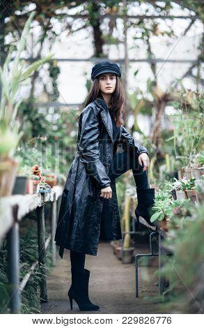 Full Length Portrait Of Trendy Hipster Girl Posing In Garden Greenhouse Background