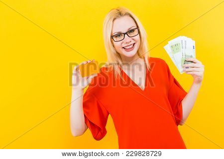 Portrait Of Woman In Glasses And Red Dress Isolated On Yellow Background Hold Blank Credit Card And