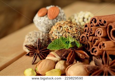 Sweets With Different Sprinkles, Cinnamon, Anise Stars, Mint And Pistachio Nuts On Wooden Boards