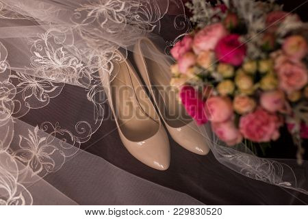 Beige Bridal Shoes And A Veil Lying On A Red Armchair. Wedding Bouquet With Purple And Pink Roses Ou