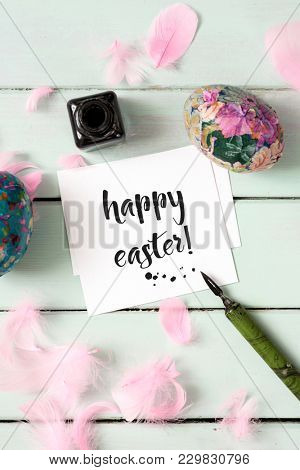 high angle view of a piece of paper with the text happy easter written in it, an ink bottle, a dip pen, some different homemade easter eggs and some pink feathers, on a pale green wooden table
