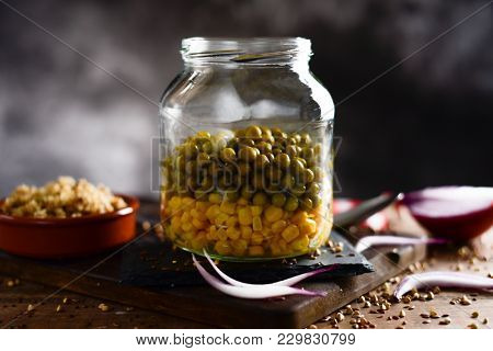 closeup of a mason jar salad in preparation, with sweet corn and green peas placed in different lays and an earthenware bowl with quinoa and some pieces of purple onion, on a rustic wooden table