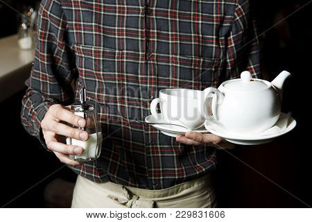 The Waiter In The Uniform Holds A Kettle In His Hands, A Cup On A Saucer And A Sugar Bowl.