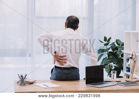 Rear View Of Mature Businessman With Backache At Office