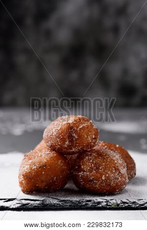 some bunyols de Quaresma, typical pastries of Catalonia, Spain, eaten in Lent, placed on a slate tray, on a table, against a dark background with some blank space on top