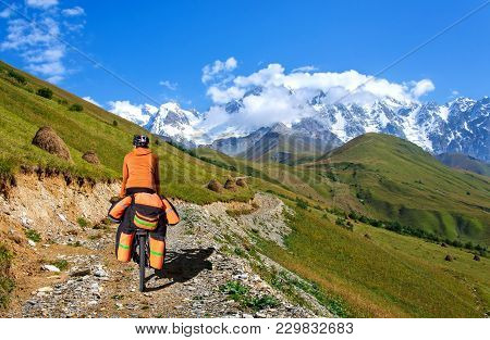 A Man On A Bicycle With A Large Backpack Rides On A Mountain Road Georgia