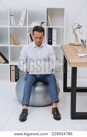 Handsome Mature Businessman Working With Laptop While Sitting On Fit Ball