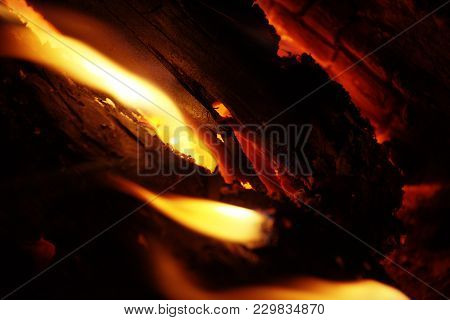 Detail View Into Fireplace Ember Wood.  Glowing Embers In Hot Red Color.