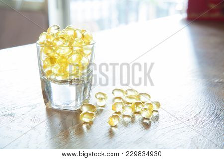 Fish Oil, Soft Capsule, Omega, Supplement In Glass On Wooden Table Background,healthy Product Concep