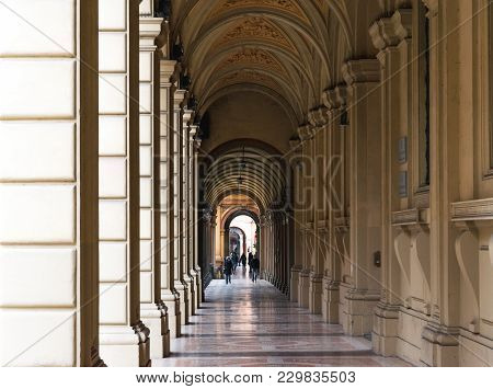 Bologna, Italy - 17 February, 2016: People Walking Through A Portico, Sheltered Walkway, In Bologna