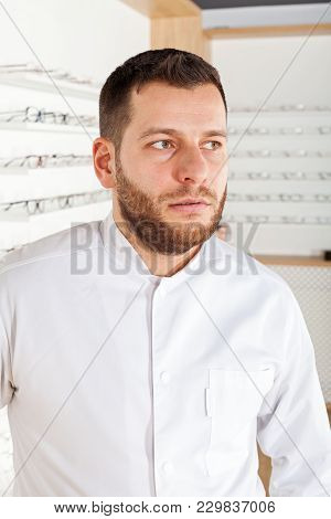 Portrait Of Handsome Ophthalmologist Wearing White Coat In Optical Store