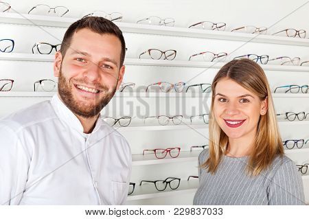 Young Ophthalmologist And Beautiful Female Patient In Optical Store Choosing Eyeglasses