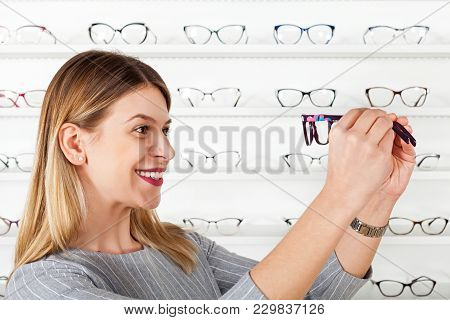 Attractive Young Woman In Optical Store Choosing Eyeglass To Correct Vision