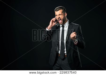Successful Businessman Yelling While Talking On Smartphone, Isolated On Black