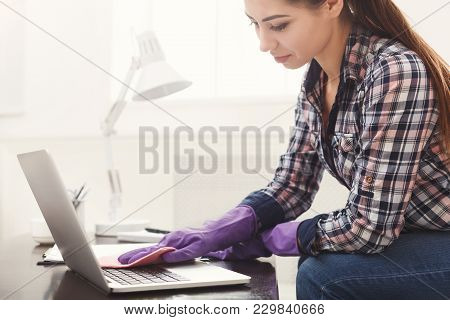 Woman Cleaning Laptop Keyboard. Young Girl Washing Computer, Spring Cleaning Concept, Copy Space