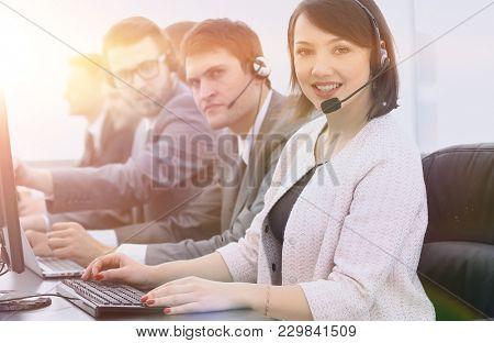 female customer service representative and colleagues in the call center