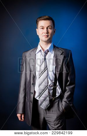 Businessman In A Grey Suit In A Photo Studio. Clothes Of The Fifties.