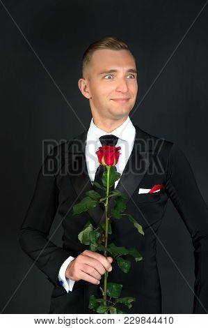 Ballroom Dancer Smile With Red Rose On Dark Background. Happy Man In Suit With Flower. Valentines Da