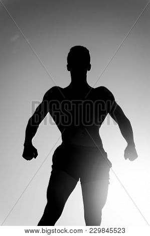 Sportsman Relaxing Muscles, Biceps, Triceps Outdoors. Bodybuilder Posing On Sky And Sun Light Backgr