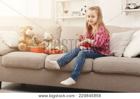Beautiful Little Girl Upwrapping Presents On Sofa At Home