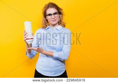 Portrait Of Attractive Blonde Woman In Blue Shirt And Eyeglasses Holding Spiral Light Bulb Isolated