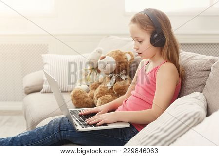 Little Girl In Earphones With Laptop At Home. Cute Child Doing Homework On Computer. Modern Online E