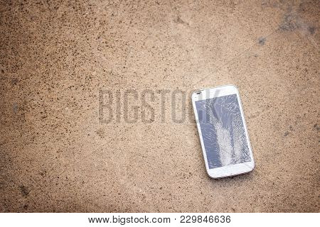 Top View Of Broken Mobile Phone Drop On Cement Floor With Copy Space For Desing, High Contrast, Shal