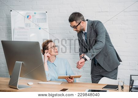 Boss Showing His Secretary His Watch To Explain That She Is Late