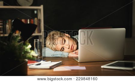 Tired Freelancer Working On Laptop At Home. Woman Put Her Head On Her Hands While Sitting At Her Wor