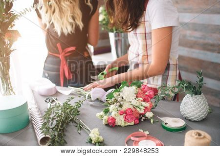 Flowers Delivery Top View. Florists Creating Order, Making Rose Bouquet In Flower Shop. Two Female F