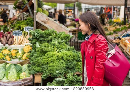 Young Asian woman buying fresh vegetables at farmers food market with shopping bag. Chinese Caucasian girl walking at outdoor stall.