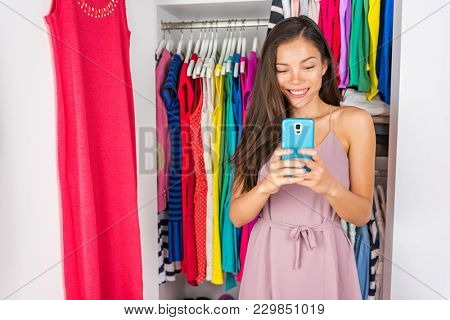 Selfie Asian girl taking photo with phone of outfit in walk-in closet dressing room. Clothes fashion stylist. Shopping girl using smartphone fashion app posting on social media.