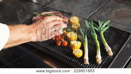 Unrecognizable Male Chef Cooking Medium Beef Steak And Vegetables On Grill. Healthy Exclusive Food P
