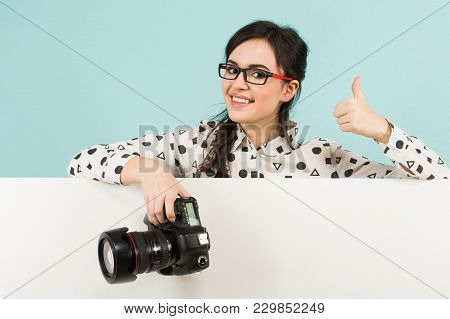 Portrait Of Young Attractive Happy Woman Photographer In White Shirt Holding Camera And Her Thumb Up
