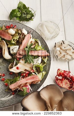 Warm Salad With Grilled Duck Breast, Mushrooms, Soft Cheese And Mix Of Greens On Gray Plate Finely D