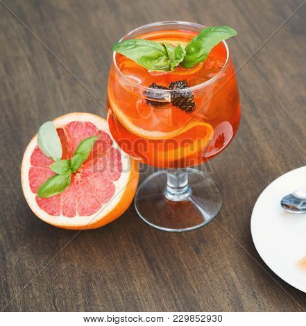 Traditional Italian Spritz Cocktail. Soft Drink With Red Bloody Orange, Prosecco And Pine Cones Conf