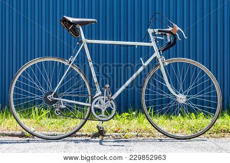 Vintage Racing Bicycle From The 60s With Chrome Steel Frame In Front Of Blue Wall And Green Grass