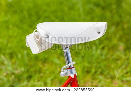 White Saddle With Saddlebag On Red Vintage Classic 1970s Folding Bike With Brurred Green Grass In Ba