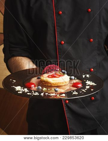 Unrecognizable Male Chef Holding Lemon Cheesecake With Berry Spheres And Caramel Decoration Served O