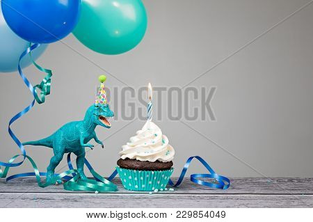 Blue Dinosaur Toy With Birthday Cupcake And Balloons On A Gray Background.