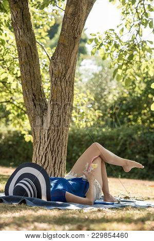 Barefoot Woman Relaxing Outdoors In The Garden In Her Sunhat Lying On The Grass In The Shade Of A Tr