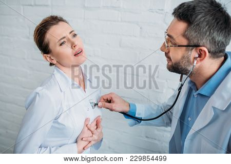Doctor Listening To Heartbeat Of Patent With Stethoscope