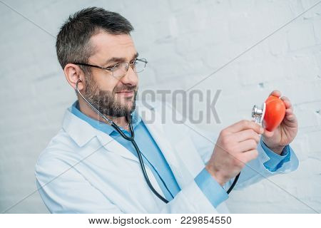 Handsome Smiling Doctor Listening Heartbeat Of Toy Heart With Stethoscopes
